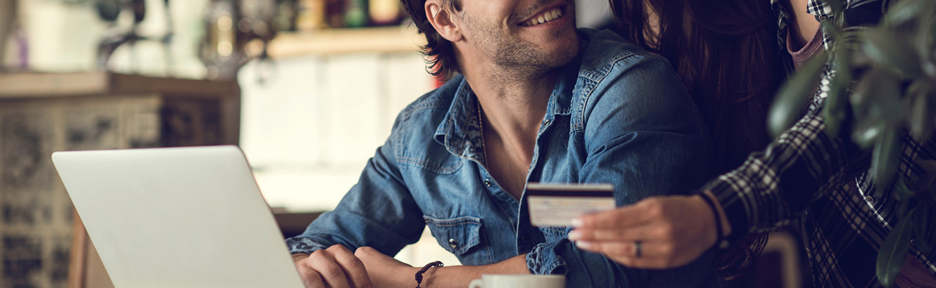 Man at laptop smiling next to woman holding debit card